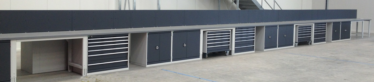 A long row of low Cubio cabinets with worktops and back panels in an automotive workshop.