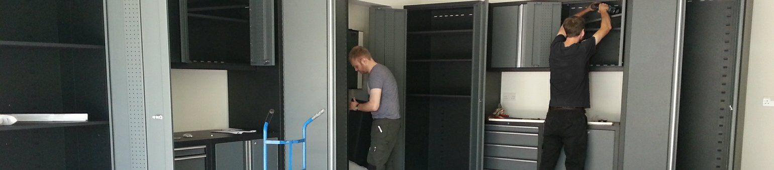 Fitters carrying out an installation of garage cupboards and worktops