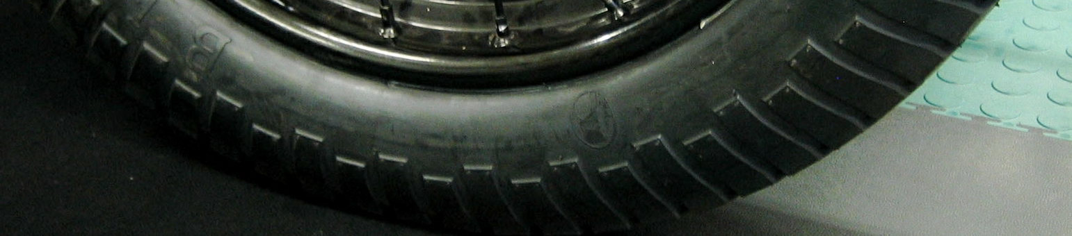 A close-up of a garage floor with a vintage car tyre parked on the green and black tiles.