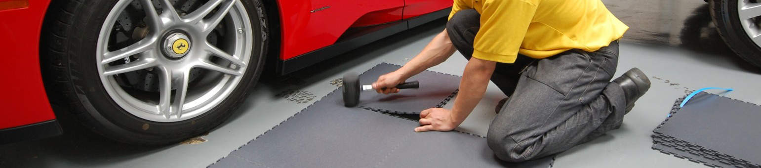 Garage flooring PVC tiles being laid using a rubber mallet next to a Ferrari.