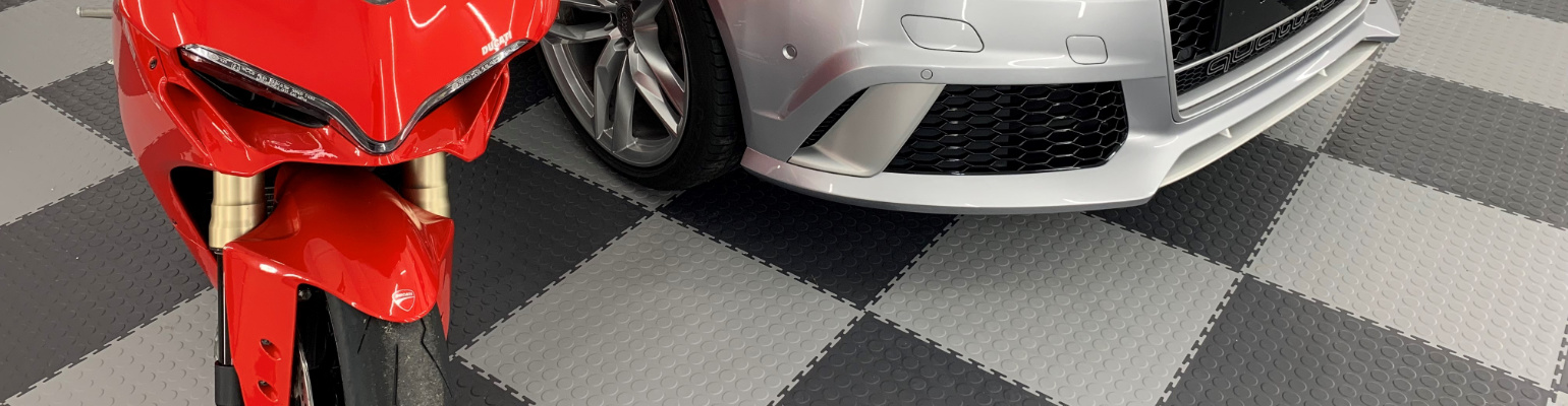 A motorcycle on a floor laid with light grey and graphite interlocking PVC tiles with a raised disk texture.