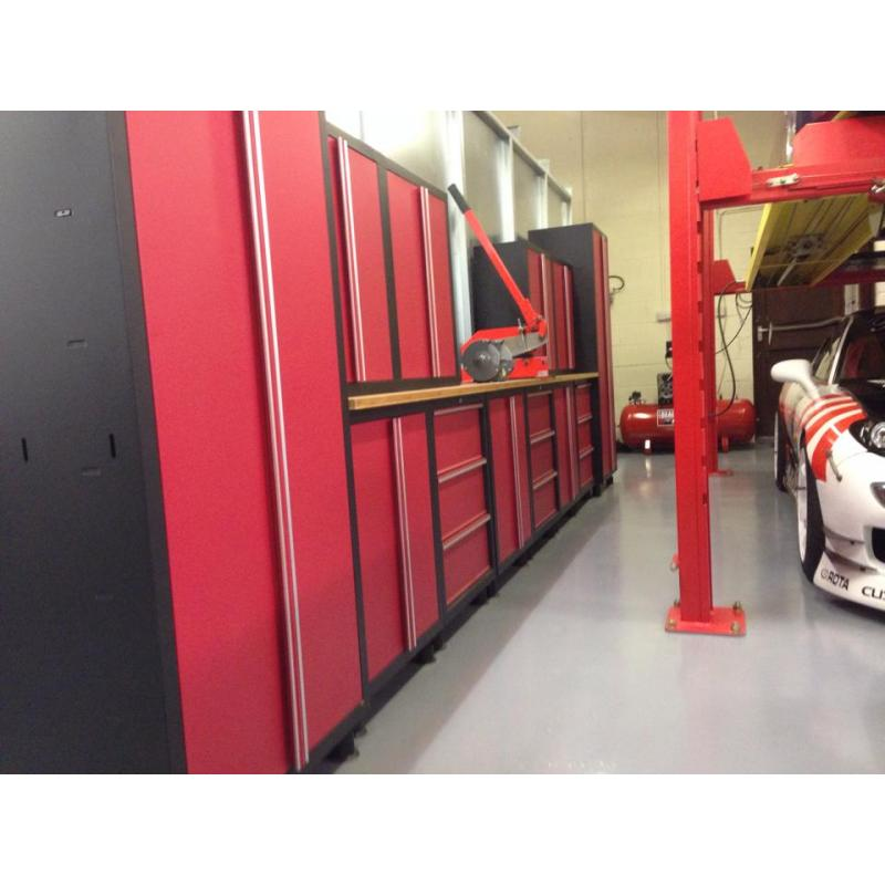 Black and red heavy duty cabinets in a vehicle detailing workshop.
