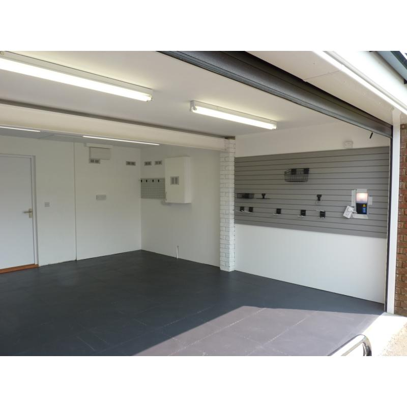Garage after - MDF cladding painted white, boxed in gas meter with ventilation grills for pipework