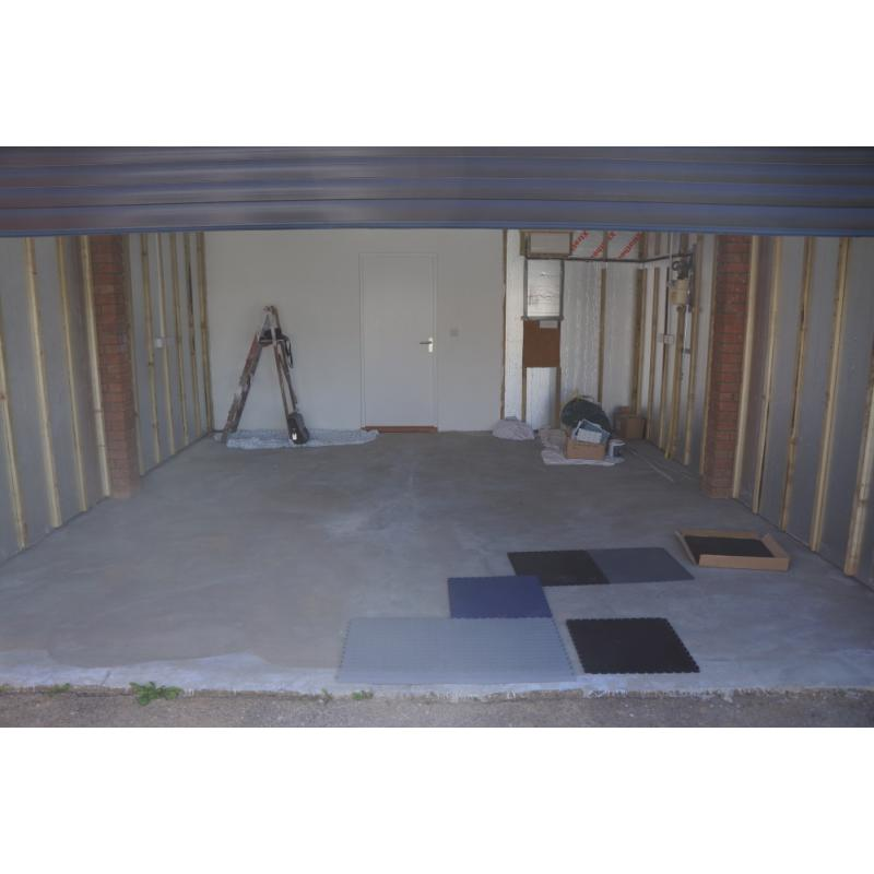 Garage before - with visible studding and concrete floor