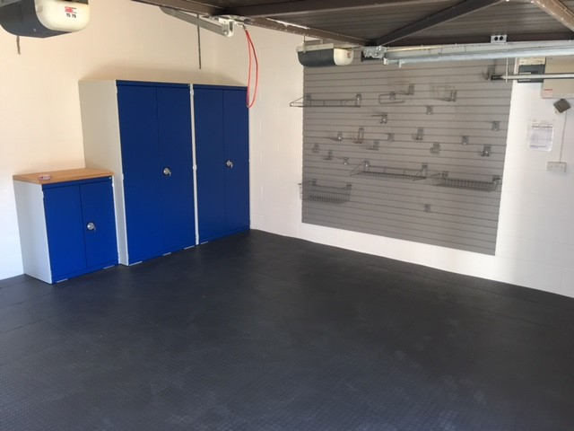 A customer photo showing his Bott Cubio cupboards, wall storage system, and garage floor tiles in graphite.