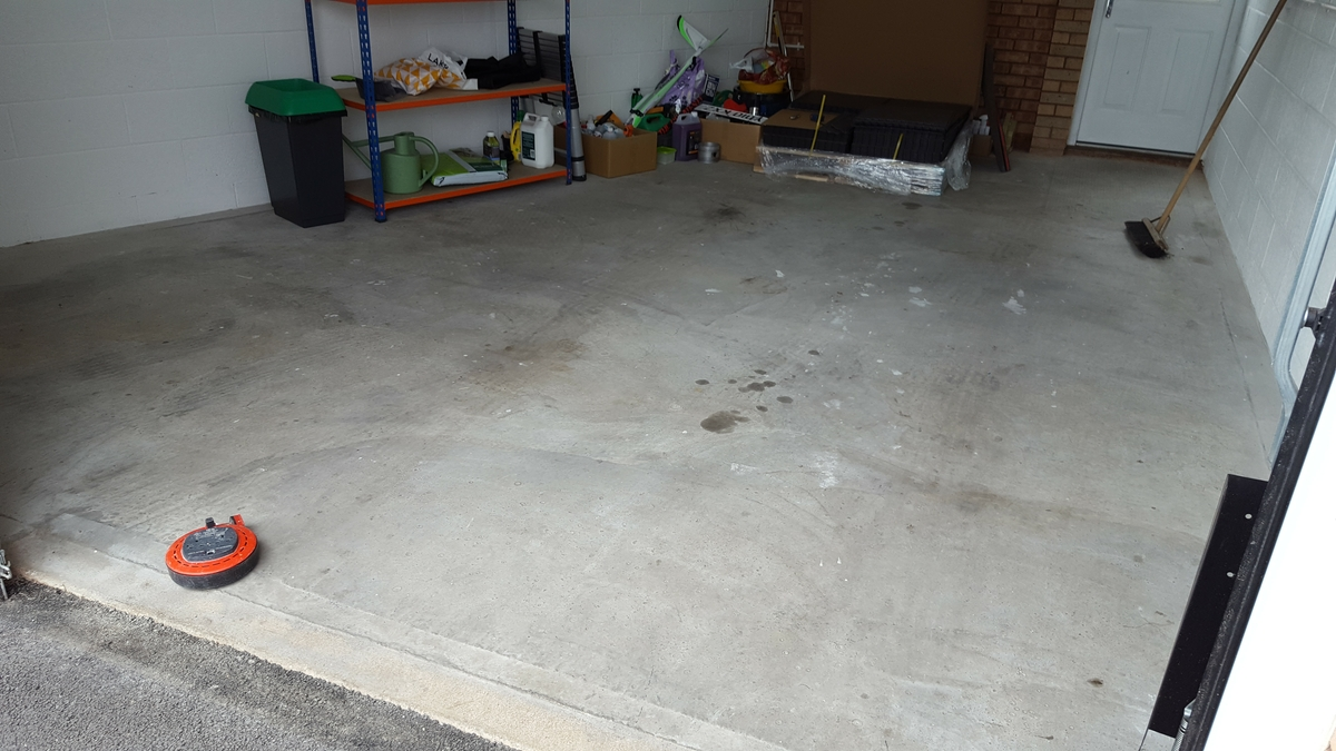 A customer's cold, dusty concrete garage floor prior to his DIY installation. Note the heavily angled wall.
