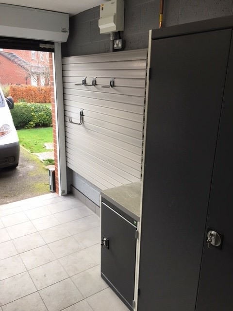 A single garage with Bott Cubio cabinets in light grey and anthracite along with a section of StorePanel (full hook kit not pictured)