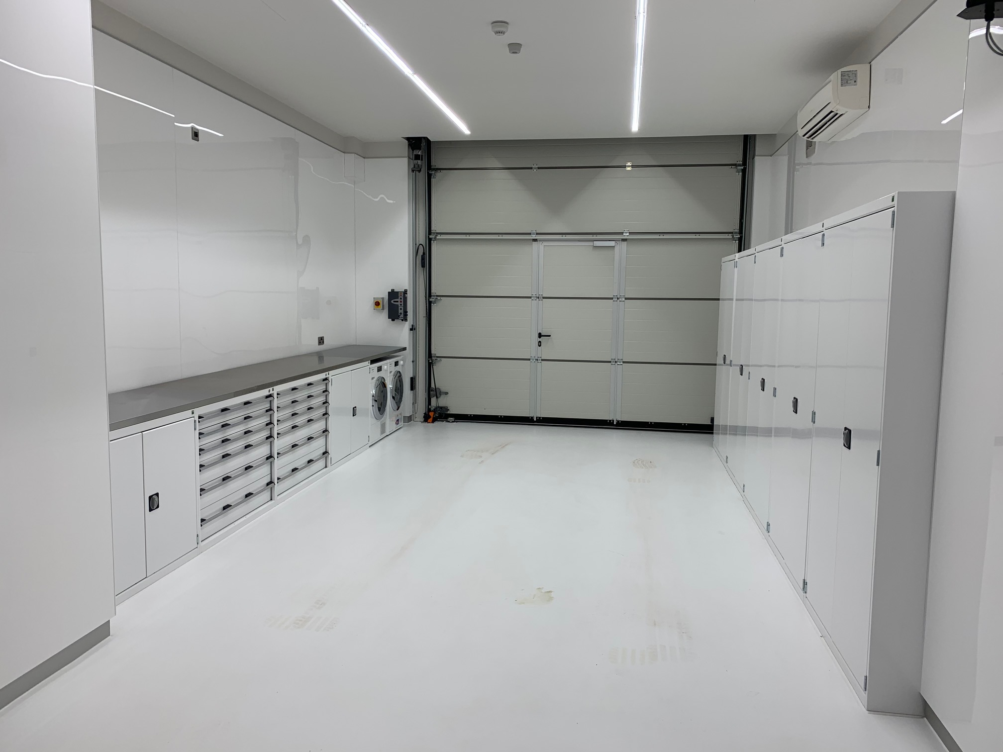 Bott Cubio cabinets supplied in custom white with custom stainless steel worktops for a prestigious garage/showroom in west London. Low cupboards and drawer units on the left, tall cupboards on the right offering huge storage capacity.