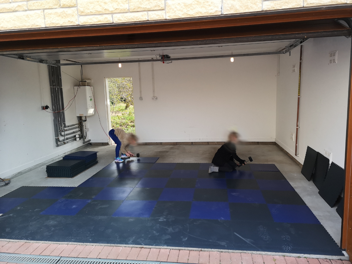 A customer's children happily banging our interlocking tiles together showing how easy they are to lay. The cement dust footprints illustrate just how much loose dust there is on a typical garage floor. This is easily swept and mopped up once the floor is finished.