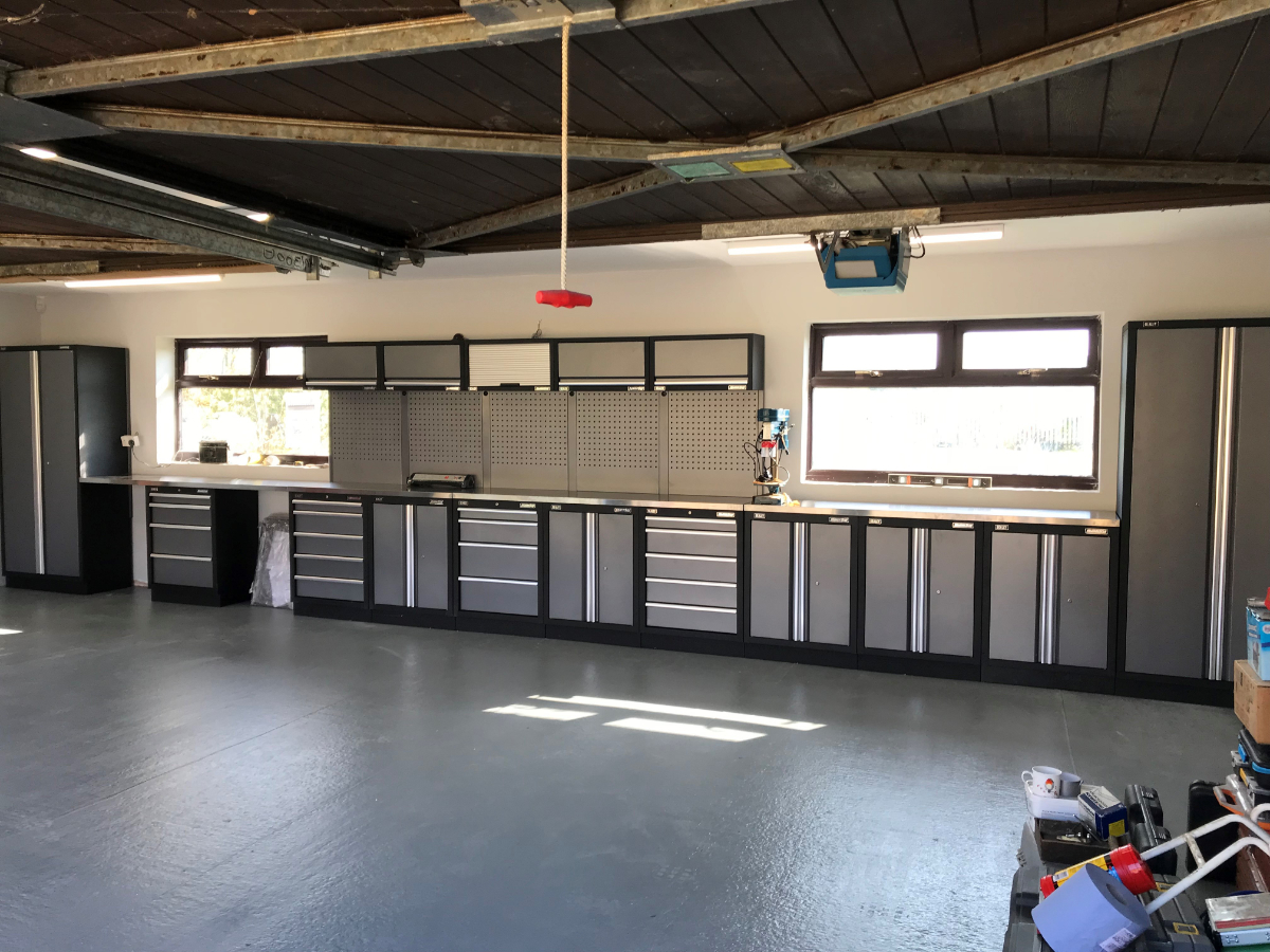 A large Northamptonshire domestic garage supplied with Sealey Superline Pro cabinets. The customer measured up and specified the perfect arrangement to fit between the windows along with a long worktop on the left to create storage or seating gaps.