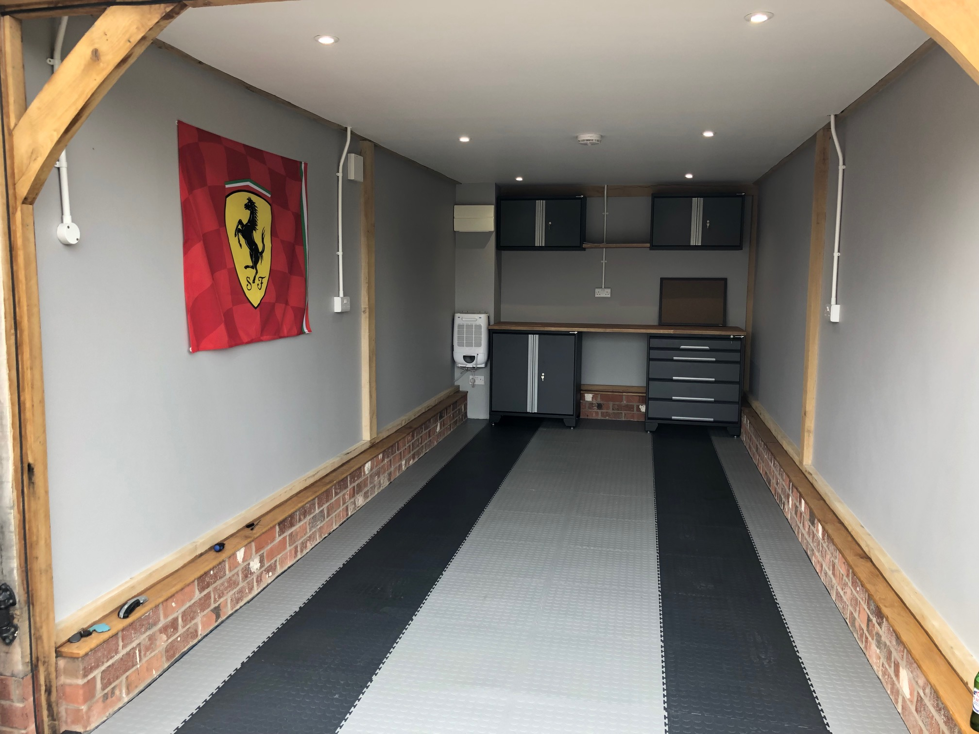 GaragePride Evoline cabinets on the rear wall, light grey 7mm interlocking PVC tiles with graphite strips where the tyres will sit.  Customer comment
