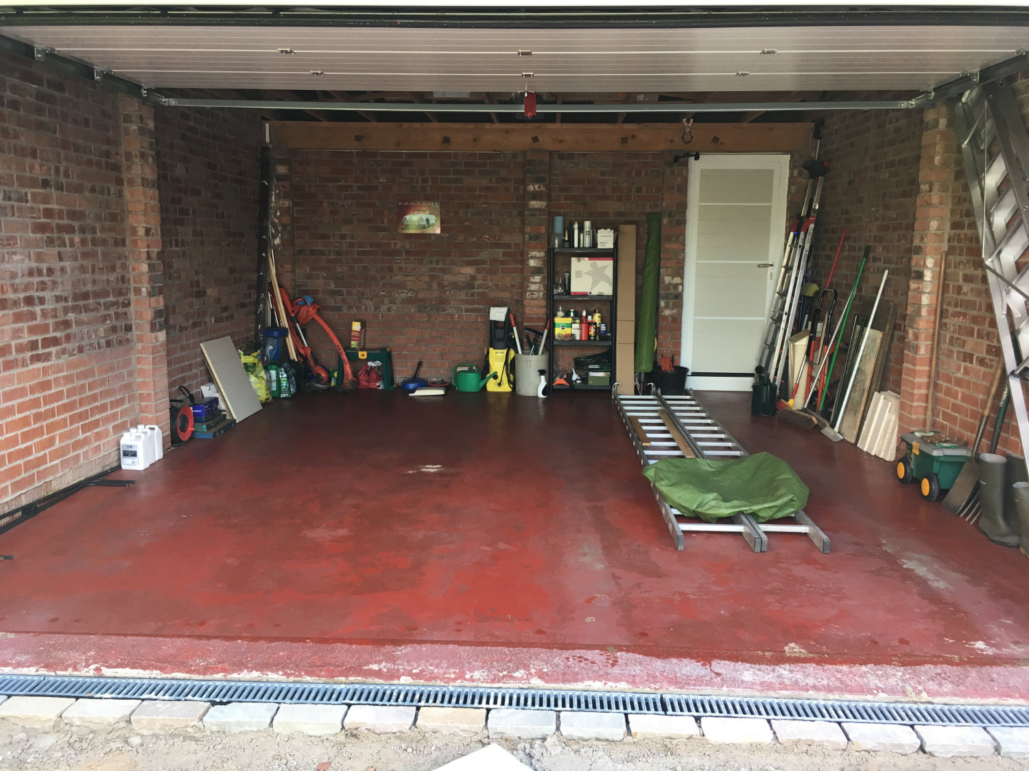 A customer's Cheshire garage before tile installation showing stained and damaged garage floor paint (many of us have been there).