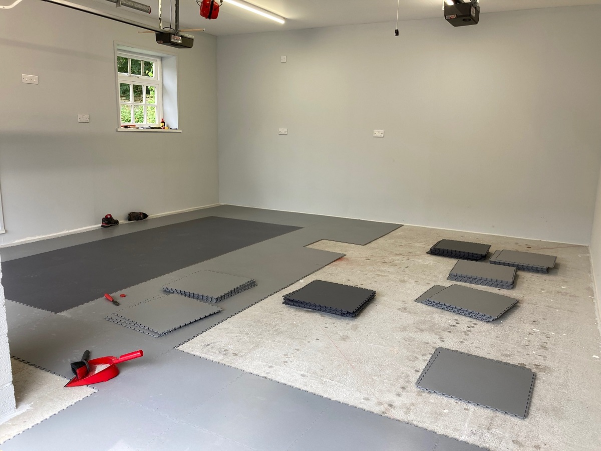 Floor tiles being laid by a customer last weekend. With a bit of careful planning he is laying two dark grey pads where car tyres will sit. This is the smooth texture Professional tile.