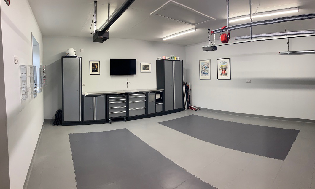 A customer's new garage ready for light car or bike maintenance. EvoTile professional tiles, cabinets with mobile tool trolley and stainless steel worktop. Very nice!